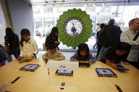 Young holiday shoppers interact with the iPad at the Apple Store during Black Friday in San Francisco, California, November 23, 2012.