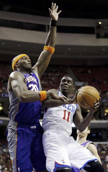 Jrue Holiday (11), de los 76ers de Filadelfia, va por la canasta ante la defensa de Jermaine O'Neal (20), de los Suns de Phoenix, en la segunda mitad de un partido de la NBA el domingo, 25 de noviembre del 2012.