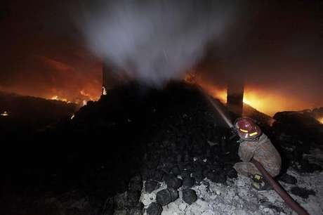 A worker calls for help as he is trapped in an 11-storey garment factory building where a fire had broken out, in the suburb of Uttara in Dhaka November 26, 2012.