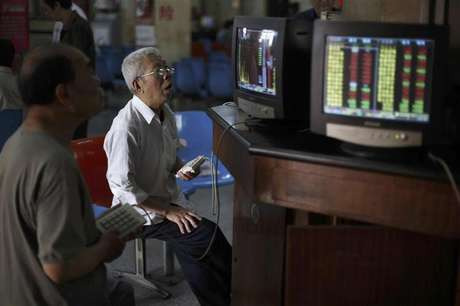Investors look at computer screens showing stock information at a brokerage house in Shanghai in this June 8, 2012 file photo. Foreign investors have started rebuilding their China equity portfolios, tempted by low valuations after two years of market underperformance and signs economic growth may be stabilizing. They have pumped nearly $4 billion (2 billion pounds) into Chinese equity funds in the past two months alone, trying to get in early on what they hope will be a sustained rally. Picture taken June 8, 2012.