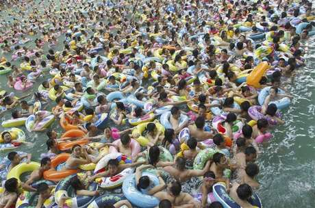 Residents crowd in a swimming pool to escape the summer heat during a hot weather spell in Daying county of Suining, Sichuan province in this July 4, 2010 file picture. China is mulling changes to its one-child policy, a former family planning official said, with government advisory bodies drafting proposals in the face of a rapidly ageing society in the world's most populous nation. Proposed changes would allow for urban couples to have a second child, even if one of the parents is themselves not an only child, the China Daily cited Zhang Weiqing, the former head of the National Population and Family Planning Commission, as saying on November 28, 2012.