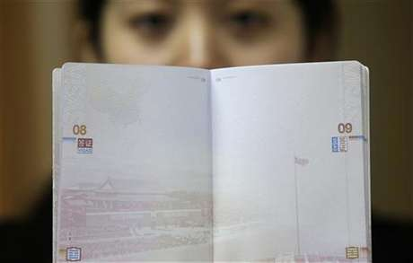 A woman holds a Chinese passport, displaying a Chinese map which includes an area in the South China Sea inside a line of dashes representing maritime territory claimed by China (L, top) and a picture of Beijing's Tiananmen Square (bottom), at an office in Wuhan airport, Hubei province, November 23, 2012. The Philippines and Vietnam condemned Chinese passports containing a map of China's disputed maritime claims on Thursday, branding the new design a violation of their sovereignty.