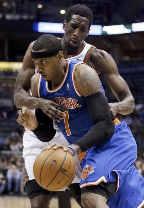 Carmelo Anthony, de los Knicks de Nueva York recibe una falta de Ekpe Udoh, de los Bucks de Milwaukee, en la primera mitad de un partido de la NBA el miércoles, 28 de noviembre del 2012.