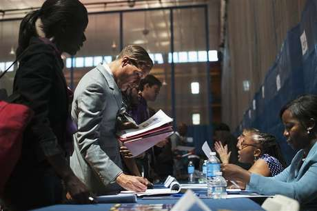 Job seekers speak to recruiters at a job fair sponsored by the New York Department of Labor in New York, June 7, 2012.