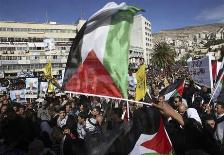 "People wave Palestinian flags during a rally in the West Bank city of Nablus, supporting the resolution that would change the Palestinian Authority's United Nations observer status from ""entity"" to ""non-member state"" November 29, 2012."