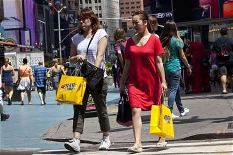 Women carry shopping bags through Times Square in New York, July 27, 2012.
