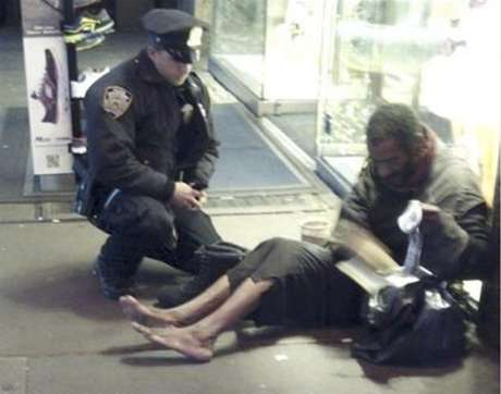New York police officer Larry DePrimo gives a homeless man a pair of boots and socks in Times Square in this November 14, 2012 handout photo courtesy of Jennifer Foster. The photograph has drawn a deluge of praise after it was published on the police department's Facebook page this week.