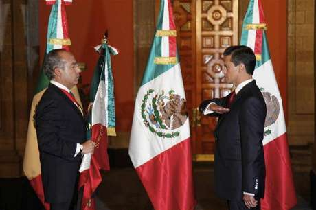 Mexico's outgoing President Felipe Calderon (L) holds the national flag as Mexico's new President Enrique Pena Nieto salutes during a midnight handover ceremony at the Palacio Nacional in Mexico City December 1, 2012.