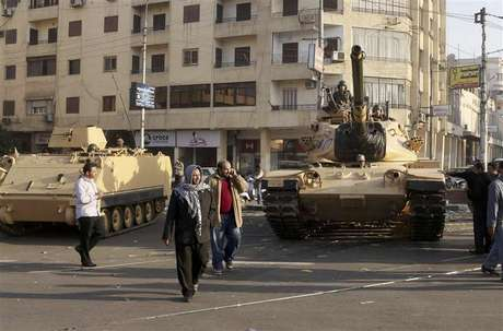 Supporters of the Muslim Brotherhood walk past tanks that were just deployed outside the Egyptian presidential palace in Cairo December 6, 2012. At least three tanks are deployed outside the palace on Thursday in a street where supporters and opponents of President Mohamed Mursi had been clashing into the early hours of the morning, a Reuters witness said.