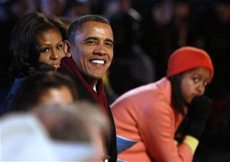 U.S. President Barack Obama (C) is joined by his daughter Malia (R) and first lady, Michelle Obama (L) as they watch the show at the official lighting of the National Christmas Tree ceremony on the Ellipse in Washington, December 6, 2012.