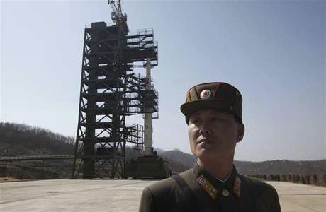 A soldier stands guard in front of a rocket sitting on a launch pad at the West Sea Satellite Launch Site, during a guided media tour by North Korean authorities in the northwest of Pyongyang in this April 8, 2012 file photo.