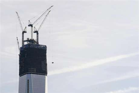 Cranes lift pieces of the spire up One World Trade Center in New York, December 12, 2012.