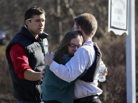 Unas personas se consuelan mutuamente en el exterior de la escuela Sandy Hook en Newtown, en Connecticut, después de registrarse el tiroteo.