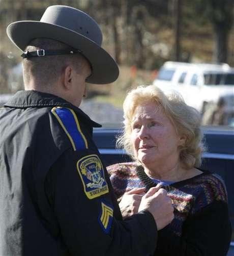Policial fala com mulher em frente à escola primária Sandy Hook após tiroteio em Newtown, nos EUA. Um total de 28 pessoas morreu depois de um tiroteio numa escola no Estado norte-americano do Connecticut e em um local próximo, informou a polícia nesta sexta-feira. 14/12/2012