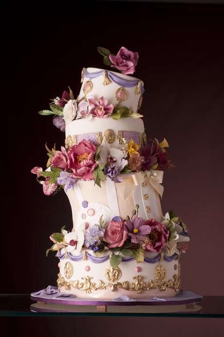 Bolo inclinado de quatro andares de banana com gianduia e capuccino coberto de pasta de açúcar e decorado com flores, The King Cake. <strong>Preço:</strong> a partir de R$ 180 o quilo