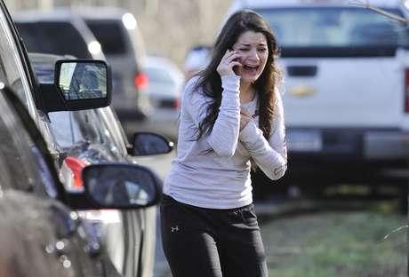 Mulher chora enquanto espera por notícias da irmã, uma professora na escola Sandy Hook