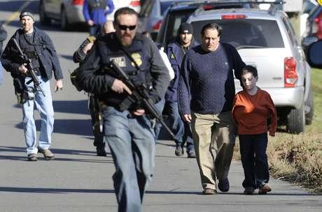 Policiais armados caminham em meio a pais que levam seus filhos embora da escola Sandy Hook