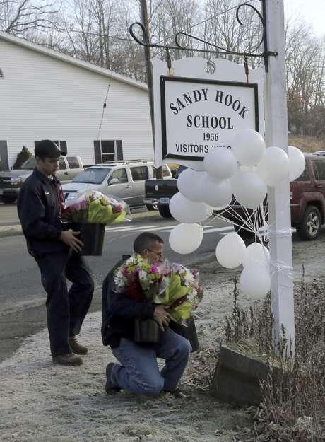 Bomberos voluntarios colocan flores en un monumento improvisado en la entrada de la escuela primaria Sandy Hook el sábado 15 de diciembre de 2012 en Newtown, Connecticut. La familia de una niña boricua de 6 años que murió asesinada en la matanza en la escuela se había mudado a Estados Unidos apenas dos meses antes de la tragedia.