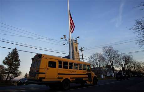 A flag is seen at half staff as a school bus passes along Main Street in Newtown, Connecticut December 14, 2012.