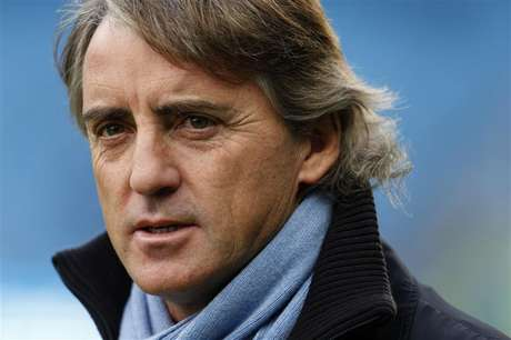 Manchester City manager Roberto Mancini walks onto the pitch before their English Premier League soccer match against Manchester United at The Etihad Stadium in Manchester, northern England December 9, 2012