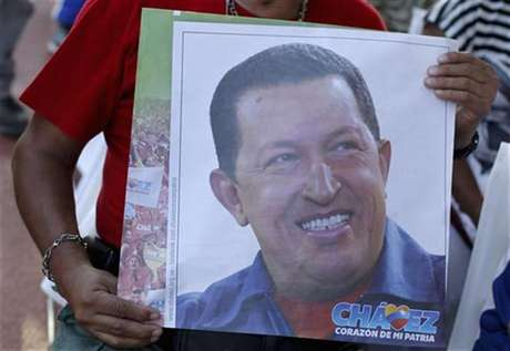 A supporter of Venezuelan President Hugo Chavez holds a picture of him, as he attends a mass to pray for Chavez's health in Caracas December 19, 2012.