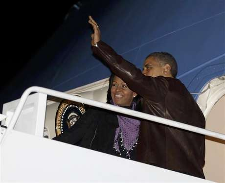 U.S. President Barack Obama waves next to first lady Michelle Obama as they prepare to depart Joint Base Andrews outside Washington, for their holiday trip to Hawaii, December 21, 2012.