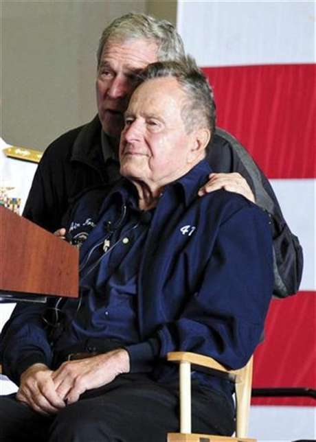 Former U.S. Presidents George W. Bush and his father George H.W. Bush attend a function onboard the USS George H.W. Bush aircraft carrier off the coast of Maine, June 10, 2012 in this U.S. Navy handout photo. The elder Bush, a former naval aviator, and his family members were attending a reenlistment ceremony on the carrier named for him.