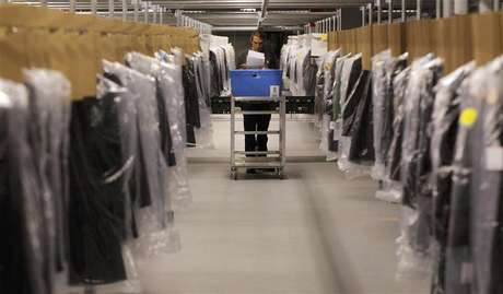 Associate Joseph Rodeheaver fills clothing orders at the Macy's-Bloomingdale's fulfillment center in Martinsburg, West Virginia in this December 6, 2012 file photograph. Macy's Inc recently opened a facility the size of 43 football fields - big enough to stock 1 million pairs of shoes - just to fulfill orders made online.