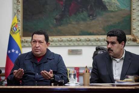 ARCHIVO - En esta foto de archivo del 8 de diciembre de 2012, difundida por el Palacio de Miraflores, el presidente venezolano Hugo Chávez habla acompañado por su vicepresidente Nicolás Maduro en el palacio presidencial en Caracas. Chávez, quien enfrenta un cuadro de salud complejo tras una operación a la que fue sometido en La Habana, delegó en Maduro algunas funciones administrativas para la emisión de créditos públicos, ajustes presupuestarios y expropiaciones, informó el gobierno el miércoles 26 de diciembre de 2012