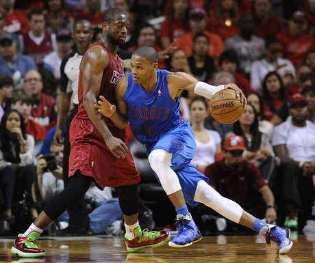 Oklahoma City Thunder's Russell Westbrook (R) is defended by Miami Heat's Dwyane Wade (L) during the first half of their NBA basketball game in Miami, Florida, December 25, 2012.