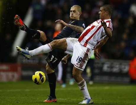 Liverpool's Martin Skrtel (L) challenges Stoke City's Jonathan Walters