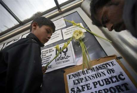 Demonstrators put flowers on the billboard of a bus stop during a protest march in New Delhi December 29, 2012.