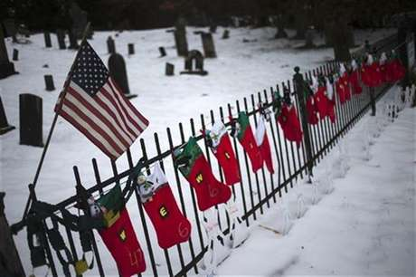 A U.S. flag hangs over stockings left as a memorial for victims of the Sandy Hook Elementary School shooting, along a fence surrounding the Sandy Hook Cemetery in Newtown, Connecticut December 27, 2012.