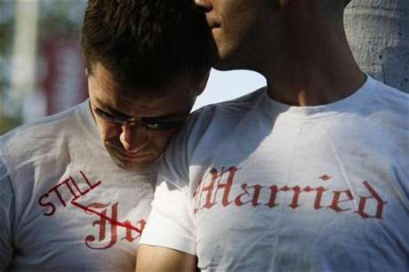 Gay couple Ethan Collings (L), 32, and his spouse Stephen Abate, 36, hug as they celebrate their one-year wedding anniversary in West Hollywood, California, June 16, 2009.