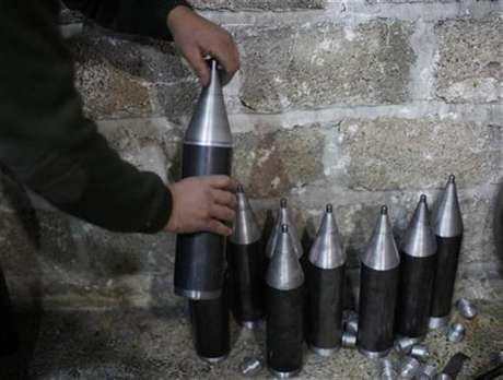 A Free Syrian Army fighter makes homemade missiles at a workshop in north Aleppo December 29, 2012.