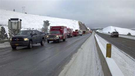 Rescue personnel respond to the scene of a charter bus crash on I-84, east of Pendleton, Oregon in this December 30, 2012 handout photo. Five people were killed and at least 20 injured in the incident. Police said the bus may have gone out of control on the highway before crashing through a guardrail and down an embankment.
