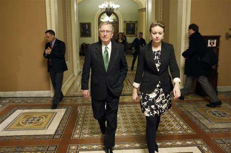 U.S. Senate Minority Leader Mitch McConnell (C) departs the senate floor with an aide after a senate vote in the early morning hours at the U.S. Capitol in Washington January 1, 2013.