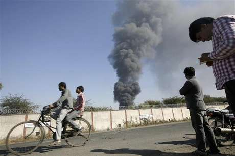 Onlookers stand as smoke billows from Indian Oil Corporation's fuel depot in Hazira, near Surat city of India's western state of Gujarat January 5, 2013. A major fire broke out at an IOC fuel depot on Saturday in Hazira with no reports of casualties or injuries, according to local media.
