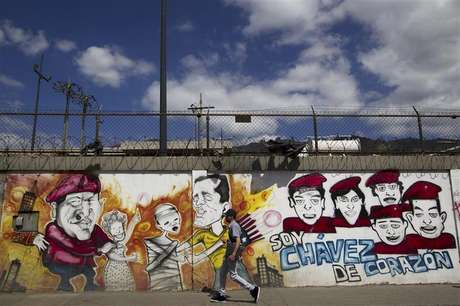 """A man walks past a mural depicting Venezuelan President Hugo Chavez in Caracas January 9, 2013. Venezuela's top court endorsed the postponement of Chavez's inauguration this week and ruled on Wednesday that the cancer-stricken president remained the South American OPEC nation's leader. The mural reads: """"I am chavez, from heart."""""""