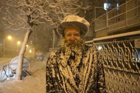 Imagem mostra homem judeu coberto de neve em Jerusalém; onda de frio rara atinge a região