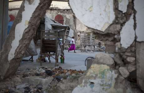 A woman walks past buildings damaged by the 2010 earthquake in downtown Port-au-Prince, Haiti, Wednesday, Jan. 9, 2013.