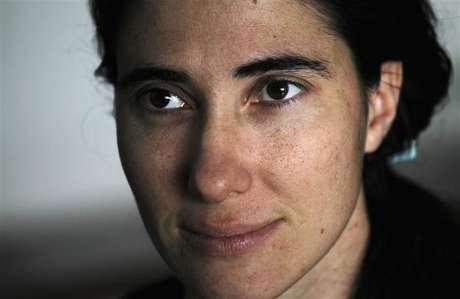 Cuban dissident blogger Yoani Sanchez listens to a question during an interview with Reuters at her home in Havana, in this February 9, 2011 file photo.
