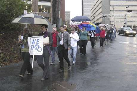 "Same-sex couples and their supporters marched through the streets of downtown Winston-Salem, North Carolina, January 14, 2013 after seeking marriage licenses that they knew they would be denied. They sang ""as long as it takes, love won't be denied"" as they walked in the rain. Holding the ""We Do"" sign at the front is Jasmine Beach-Ferrara, executive director of the Campaign for Southern Equality, which is leading the ""We Do"" push for marriage equality in seven Southern states in January. She also is a minister in the United Church of Christ."