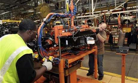Ford Assembly workers install a battery onto the chassis of a Ford Focus Electric vehicle at the Michigan Assembly Plant in Wayne, Michigan November 7, 2012.