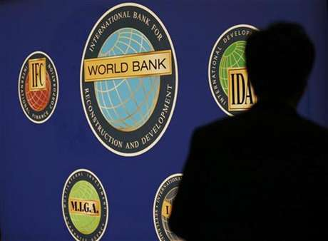 A man is silhouetted against the logo of the World Bank at the main venue for the International Monetary Fund (IMF) and World Bank annual meeting in Tokyo October 10, 2012.