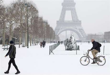 A man rides a Velib self-service public bicycle as he makes his way along a snow-covered area at the Champs de Mars near the Eiffel Tower in Paris January 19, 2013.