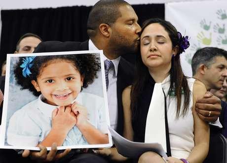 Jimmy Greene, a la izquierda, besa a su esposa Nelba Márquez Greene, mientras él sostiene un retrato de la hija de ambos, Ana, una de las víctimas de la matanaza a tiros en la escuela Sandy Hook, en una conferneica de prensa en Newtown, Connecticut, el lunes 14 de enero de 2013.