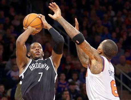 Nets vs. Knicks: Joe Johnson (7) lanza un triple ante la marca de J.R. Smith (8).