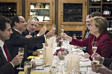 German Chancellor Angela Merkel (R) and French President Francois Hollande salute to each other during a private dinner in a Berlin restaurant at the eve of celebrations to mark the 50th anniversary of the Elysee Treaty, January 21, 2013.