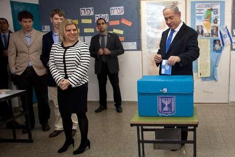 O premiê israelense, Benjamin Netanyahu, deposita seu voto ao lado da esposa Sara